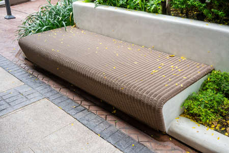 wooden chair or wood bench with concrete structure along a walkway. Rest area along pedestrain way.