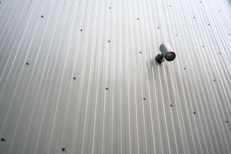 Black spot light hanging on metal sheet wall on outdoor public area.