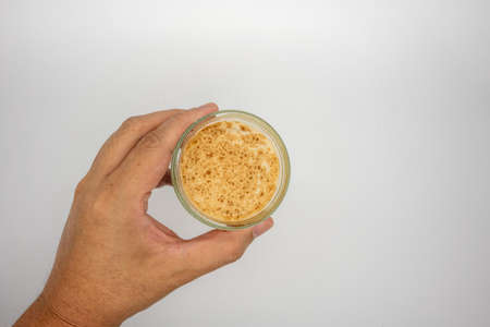 Hand holding dirty coffee on top of cold milk isolated on white background.