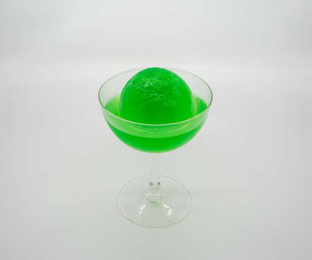 Green Apple Soda ice ball in clear cocktail glass isolated on white background. Stock fotó