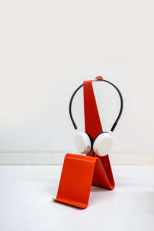 Modern red curve metal stand for wireless headset isolated on white background.