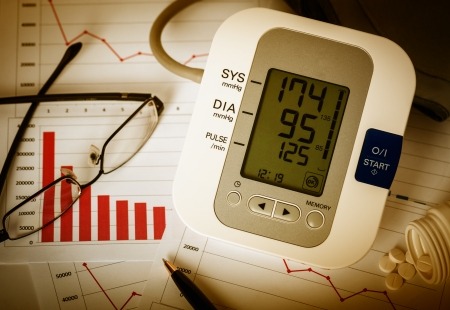 office physical pressure paper: Working late at office. Digital blood pressure monitor, glasses, pen and pills on financial reports.