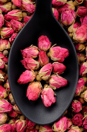 Top view of black spoon full of roses for tea Standard-Bild