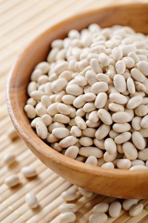 Wooden bowl full of white beans photo
