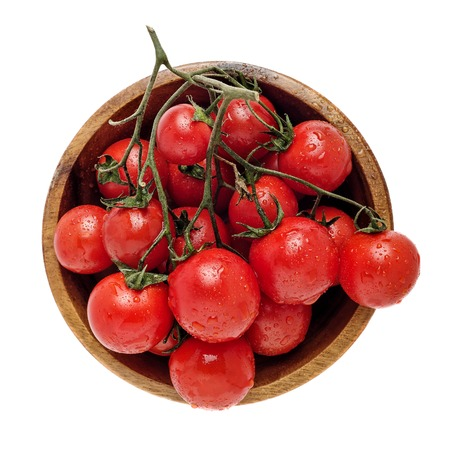 Top view of wooden bowl full of tomatoes