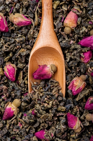 Top view of wooden spoon on oolong tea with roses
