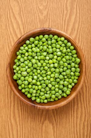 Wooden bowl full of fresh peas
