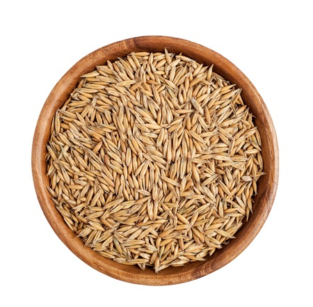 Top view of wooden bowl full of oat grains