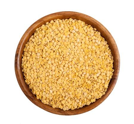 Wooden bowl full of yellow lentils Standard-Bild