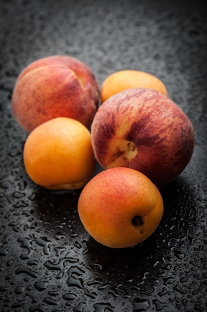 Ripe apricots and peaches on black table after rain