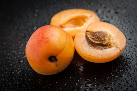 Apricot with halves on black table after rain