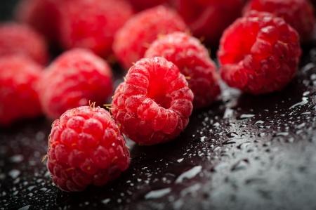Fresh raspberries on black table after rain
