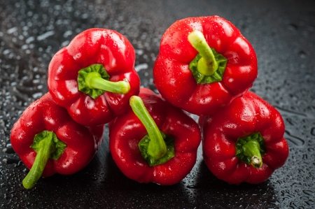 Three red bell peppers on black table after rain