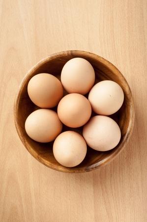 Top view of eggs inside wooden bowl Standard-Bild