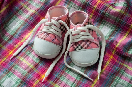 Pair of red and white sneakers on colorful fabric Standard-Bild