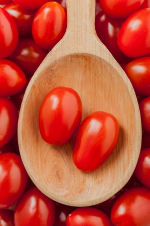 Wooden spoon with some cherry tomatoes on it