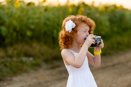 Red-haired girl in a white dress having fun photographing