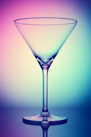 Empty coctail glass on colorful background