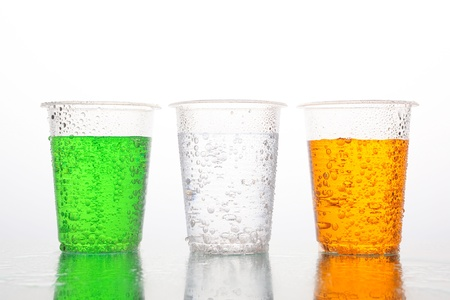 Three plastic cups with different color of carbonated beverages on white background. Green, uncolored and orange drinks. photo