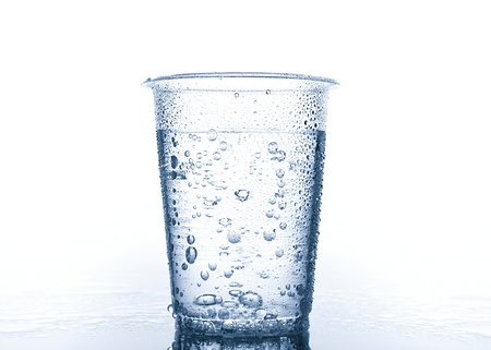 water spray: Plastic cup with water on wet surface