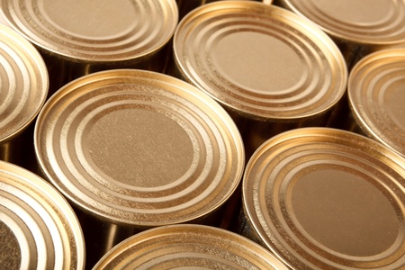 canned food: Row of the closed metal cans of yellow colour. Diagonal top view.