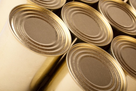 Row of the closed metal cans of yellow colour. Diagonal top view. photo