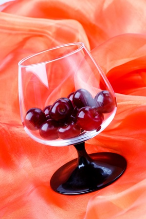 tumbler: brandy footed tumbler with cherries on red fabric