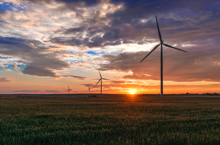 poetic: Apulia (Italy) - Wind farm with rock ruins, wind turbines and bales of hay at sunset