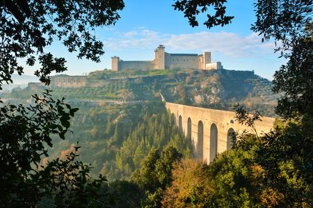 Spoleto (이탈리아) - Umbria 지역의 매력적인 중세 마을에서 안개가 낀 날. 연약한 안개는 짙은 안개에 달려 있지만 태양 광선과 함께 분위기를 연상케합니