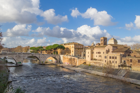 Rome, Italy - 16 December 2017 - The Tiber river and the monumental Lungotevere. Here in particular the the 'Isola TIberina' island with bridge and church