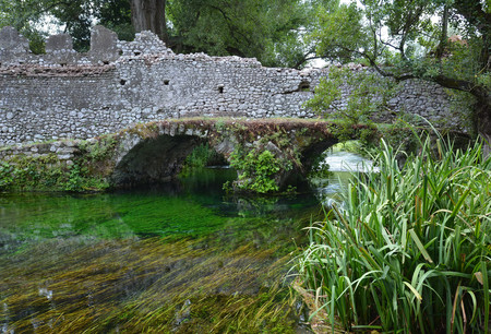 Garden of Ninfa, Italy - 21 July 2013 - A natural monument with medieval ruins in stone, flowers park and a awesome torrent with little fall. Province of Latina, Lazio region, central Italy. Editorial