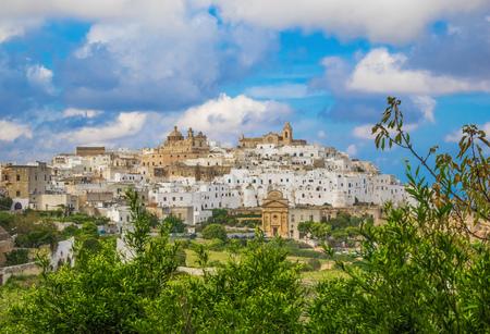 オストゥーニ(プーリア、イタリア) - 丘の上と海の横に古い歴史的中心部を持つブリンディジ、プーリア州、南イタリアの州の豪華な白い都市 写真素材