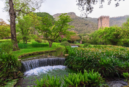 Garden of Ninfa, Italy - 15 April 2018 - A private park managed by the Caetani Foundation, with medieval ruins in stone, many flowers and a torrent with little fall. Province of Latina, Lazio region, central Italy.