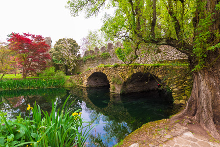 Garden of Ninfa, Italy - 15 April 2018 - A private park managed by the Caetani Foundation, with medieval ruins in stone, many flowers and a torrent with little fall. Province of Latina, Lazio region,