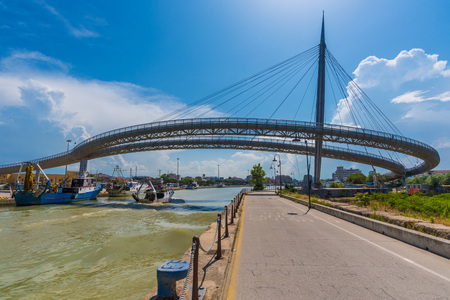 Pescara, Italy - 31 May 2018 - The Bridge of the Sea monumental bridge and the Ferris wheel on the beach, in the canal and port of Pescara city, Abruzzo region
