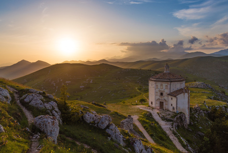 Rocca Calascio (Italy) - The ruins of an old medieval village with castle and church, over 1400 meters above sea level on the Apennine mountains in the heart of Abruzzo, at sunset. Фото со стока