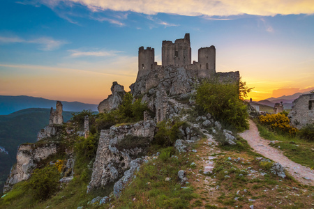 Rocca Calascio (Italy) - The ruins of an old medieval village with castle and church, over 1400 meters above sea level on the Apennine mountains in the heart of Abruzzo, at sunset. Standard-Bild