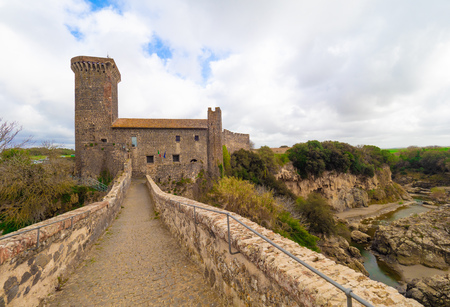 Vulci, Italy - 10 March 2019 - The medieval castle of Vulci, now museum, with Devil's bridge. Vulci is an etruscan ruins city in Lazio region, on the Fiora river between Montalto di Castro and Canino.