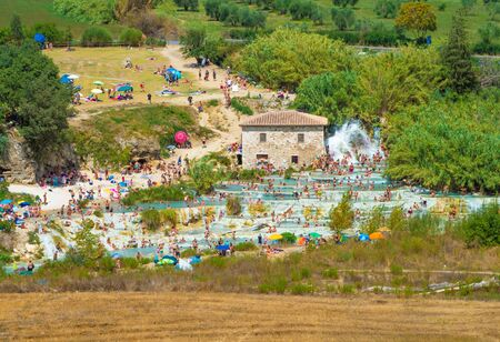 Saturnia, Italy - 15 August 2019 - The thermal waters and little village of Saturnia in the municipal of Manciano, province of Grosseto, Tuscany region 写真素材 - 129933786