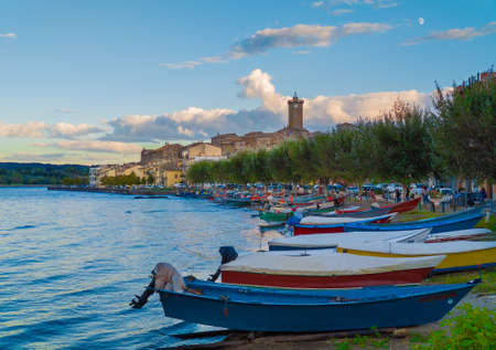 Marta, Italy - 26 September 2020 - A little medieval town on Bolsena lake with suggestive tower in stone; province of Viterbo, Lazio region. Here a view at sunset.