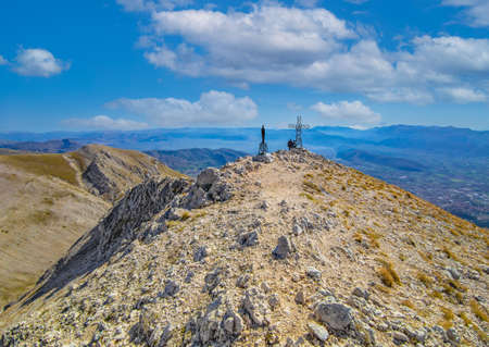Mount Velino (Abruzzo, Italy) - The cross with hikers in the landscape summit of Mount Velino, one of the highest peaks of the Apennines mountain, 2487 meters.