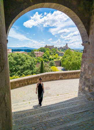 Tuscania, Italy - 2 June 2020 - A spring view with girl tourist in the historical center of this etruscan and medieval town in province of Viterbo, Tuscia, Lazio region, touristic attraction.