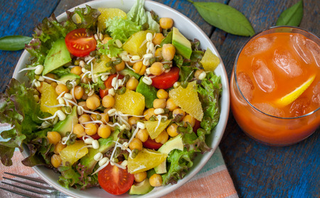 mung: Healthy green salad with orange, avocado, tomatoes, sprouts of mung bean, citrus juice. Perfect for the detox diet or just a healthy meal.  Love for a healthy raw food concept. Stock Photo
