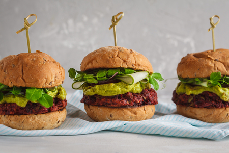 Vegan beet burgers with vegetables, guacamole and rye bun with green juice. Healthy vegan food concept.