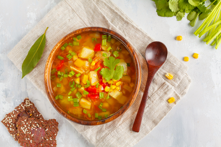 Healthy bright vegetable corn soup with a root of a herring, pepper, an onion in a wooden bowl with crispy bread. Vegan Healthy Food Concept. Top view Stockfoto