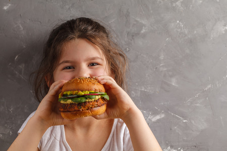 The little girl is eating a healthy baked sweet potato burger with a whole grains bun, guacamole, vegan mayonnaise and vegetables. Child vegan concept Foto de archivo