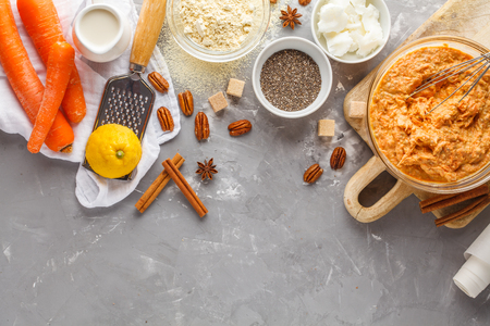 Healthy baking of carrot cake, vegan dessert ingredients: in a bowl, chia, coconut butter, almond milk, nuts. Carrot bread, gray background. Stock Photo - 95059604