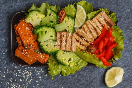 Vegetarian asian salad with sweet potato, grilled tofu, broccoli and pecan. Healthy vegan food concept. Top view, dark background
