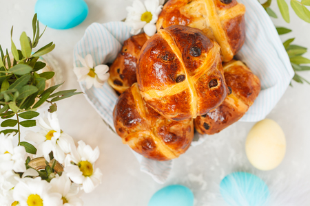Easter cross buns in a wooden box, painted eggs. Light background, copy space, Easter food concept. Stock Photo