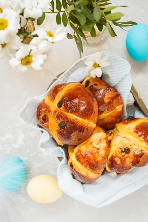 Easter cross buns in a wooden box, painted eggs. Light background, copy space, Easter food concept. Stockfoto